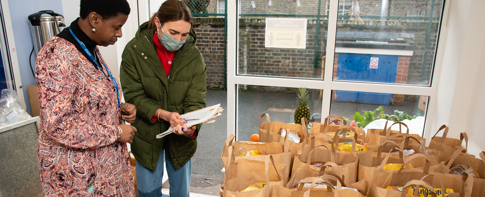 Staff wearing masks coordinating bags of food