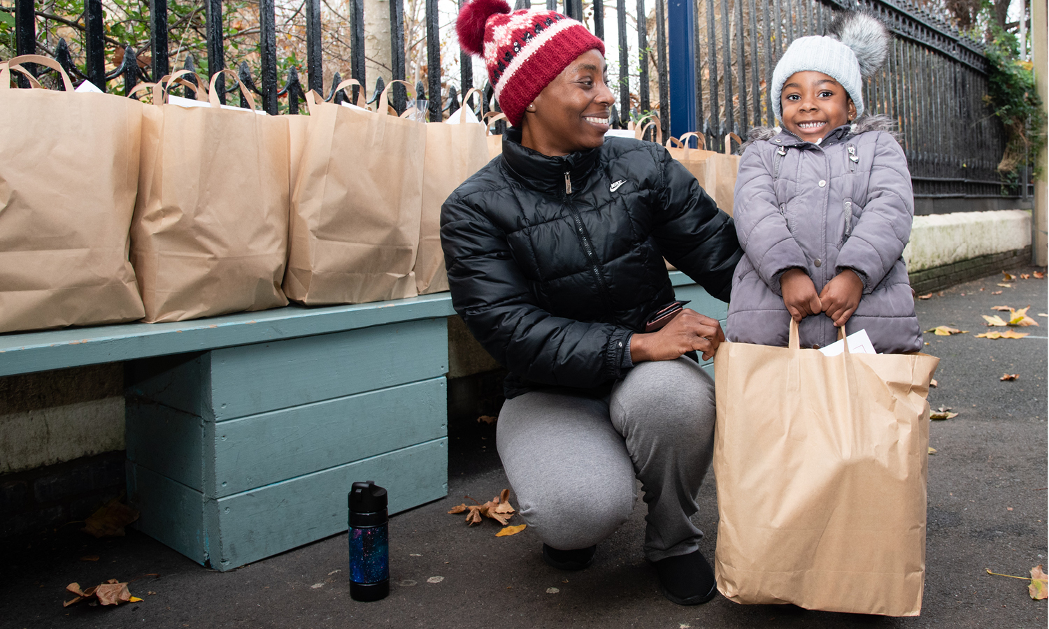 Mum and daughter smiling with food package